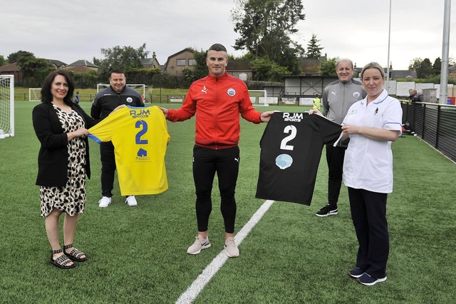 The back of Dunipace FC's new home and away strips for the 2021-2022 season feature Strathcarron Hospice and Maggie's Forth Valley logos respectively. Pictured: Cristina Pouso, Maggie's Forth Valley fundraising manager; John Marshall, club chairman; Danny Ashe, captain; Cameron Shanks, kitman; and Rozalja Glowacki, Strathcarron staff nurse. Picture: Michael Gillen.