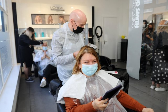Rod Smith tends to customer Margaret Murray's hair as Rod Smith Hairdressing reopens