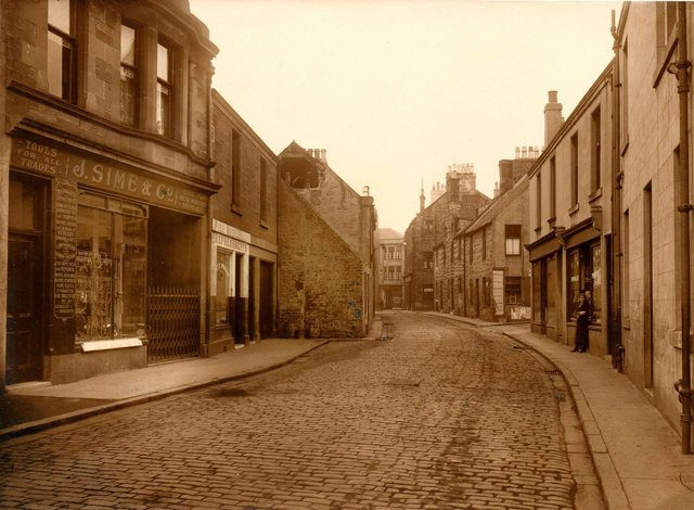 A view of Cow Wynd looking towards the High Street, with the long gone ironmongers shop Sime'son the far left. The Wynd was originally just 13ft wide.