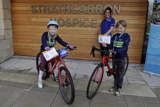 Strathcarron Hospice ward sisterSusan Bateman thanks Falkirk Junior Bike Club members Carly Scott, 7, and Freya McQueen, 8, for the group's fundraising efforts on behalf of the Fankerton service. Picture: Michael Gillen.